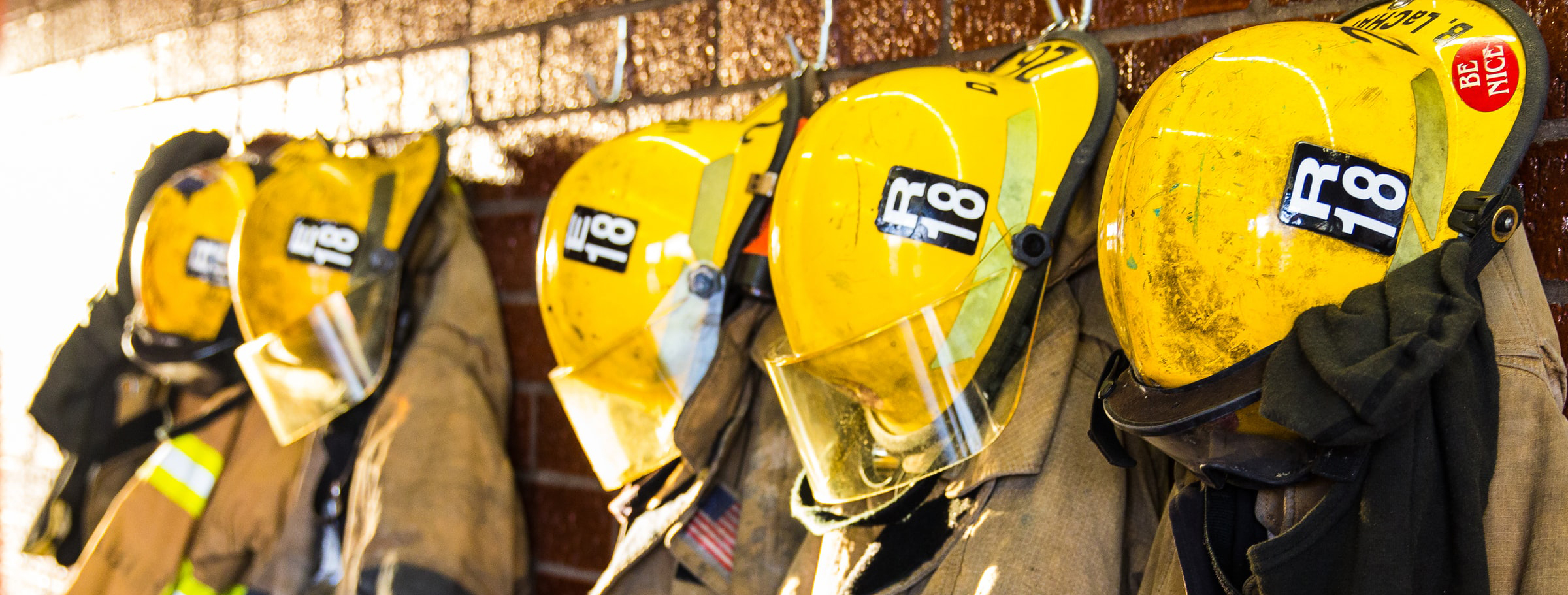 A line of firefighter suits hanging on hooks
